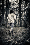 Scared girl running. Teenage girl running scared away from camera in woods stock image