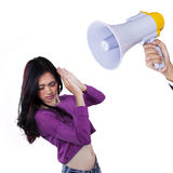 Scared girl scolded with a megaphone. Pretty teenage girl with casual clothes scolded with a megaphone in the studio Stock Image