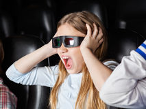 Scared Girl Screaming While Watching 3D Movie. In cinema theater Royalty Free Stock Photography