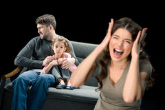 Scared girl sitting with father on couch while mother screaming at camera. Family problems concept Stock Images
