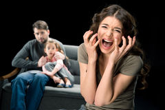 Scared girl sitting with father on couch while mother screaming at camera. Family problems concept Royalty Free Stock Image