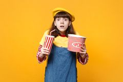Scared girl teenager in french beret, denim sundress hold plastic cup of cola or soda, bucket of popcorn isolated on. Yellow background. People sincere emotions royalty free stock photos