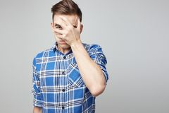 Scared guy dressed in a plaid shirt and jeans closes his face with his hand on a white background in the studio.  royalty free stock image