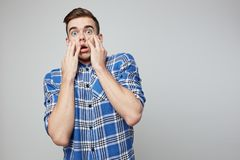 Scared guy dressed in a plaid shirt is on a white background in the studio stock image