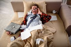 Panicked adult male yelling in bedroom. Scared guy lying in bed and screaming. He is looking at camera with frightened look and holding a briefcase. Top view Royalty Free Stock Images