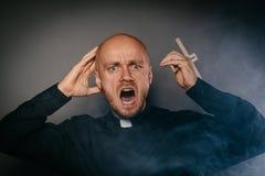 Scared ha spaventato il prete cattolico nello shir nero immagini stock libere da diritti