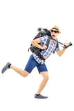 Scared hiker with backpack and camera running away Royalty Free Stock Photography