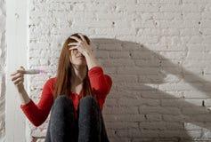 Scared a inquiété la fille enceinte d'adolescent ou la jeune femme désespérée tenant l'essai de grossesse positif photo libre de droits