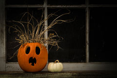 Scared Jack-O-Lantern. Close up view of Jack-O-Lantern sitting on a window ledge in front of an old rustic window royalty free stock photo