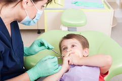 Scared kid in dentist office covering mouth Stock Images