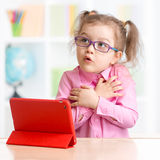 Scared kid with tablet PC in spectacles Royalty Free Stock Photo
