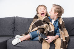 Scared kids in blanket sitting on sofa and looking at each other. Isolated on white Stock Image