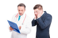 Scared lawyer and his doctor. Analyzing medical results from clipboard on white background Stock Images