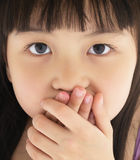Scared little girl covering mouth with hand Royalty Free Stock Photography