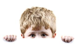 Scared little boy. Little boy looking scared and hiding behind a white background Stock Photography