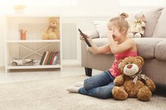 Scared casual little girl watching tv while sitting on the floor at home. Scared little casual girl watching tv. Frightened female kid sitting on the floor Royalty Free Stock Photography