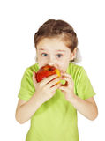 Scared little girl bites a big red apple Stock Image