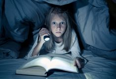 Scared little girl reading scary book under bed cover holding a flashlight late at night royalty free stock photography