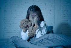 Scared little girl covering face with hands in fear in darkness at night. Scared little girl sitting in bed covering her face with hands holding her teddy in stock photo