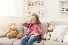 Scared little girl watching tv sitting on sofa. Scared little casual girl watching tv. Frightened female kid sitting on sofa with closed eyes, home alone Royalty Free Stock Photos