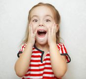 Scared little girl with wide open mouth and big eyes. Scared little adorable girl with wide open mouth, big bright brown eyes and hands on cheeks dressed in Royalty Free Stock Images