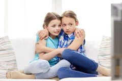 Scared little girls watching horror on tv at home. People, children, television, friends and friendship concept - two scared little girls watching horror on tv Royalty Free Stock Photos