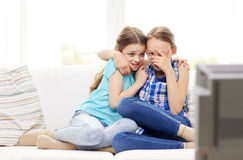 Scared little girls watching horror on tv at home Stock Image