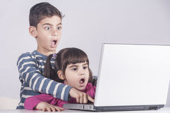 Scared little kids react while using a laptop Royalty Free Stock Photo