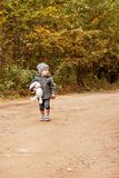 Scared Lost Boy Walking And Looking People In The Forest In A Gray Coat With A Toy Rabbit And Mushroom In His Hand Royalty Free Stock Photography