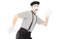 Scared male mime artist running away Stock Photo