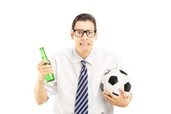 Scared male in shirt holding a beer bottle and football Stock Photos