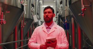 Scared male worker in white lab coat holding tablet and walking through rows of steel brewing vats. Alert signals and