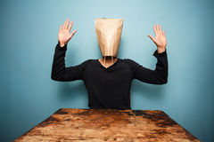 Scared man with bag over head. Sitting at a table with his hands up Stock Images