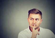 Scared man with finger on lips stock photography