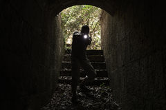 Scared man with a flashlight enters tunnel Stock Photos