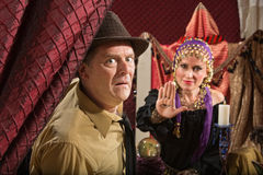 Scared Man with Fortune Teller. Scared businessman and fortune teller displaying the evil eye royalty free stock photo