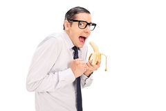 Scared man with glasses eating a banana Stock Image