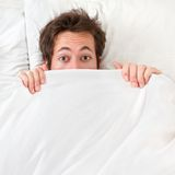 Scared man hiding in bed. Under the sheets. Funny concept image with young caucasian male model home in bed Stock Photo