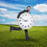 Scared man holding big white clock Royalty Free Stock Images