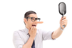 Scared man with long nose looking in a mirror Stock Images