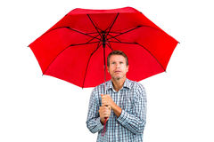 Scared man looking up while holding red umbrella Stock Image