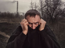 Scared man on nature. Scared man hides his face in sweater on nature Royalty Free Stock Photography