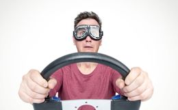 Scared man with open mouth in stylish goggles with steering wheel, car driver concept. Front view royalty free stock photography