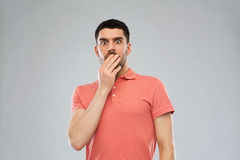 Scared man in polo t-shirt over gray background Royalty Free Stock Photo