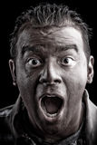 Scared Man Screaming. A frightened man with dark skin has a shocked or surprised look on his face Stock Image