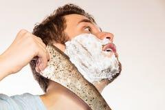 Scared man shaving having fun with machete. Stock Photo