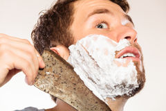 Scared man shaving having fun with machete. Royalty Free Stock Photos