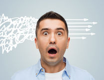 Scared man shouting. Fear, emotions, horror and people concept - scared man with big eyes and open mouth shouting over gray background Stock Photo