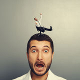 Scared man with small crazy man on the head. Portrait of scared man with small crazy man on the head Stock Images