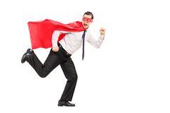 Scared man in superhero costume running Stock Images